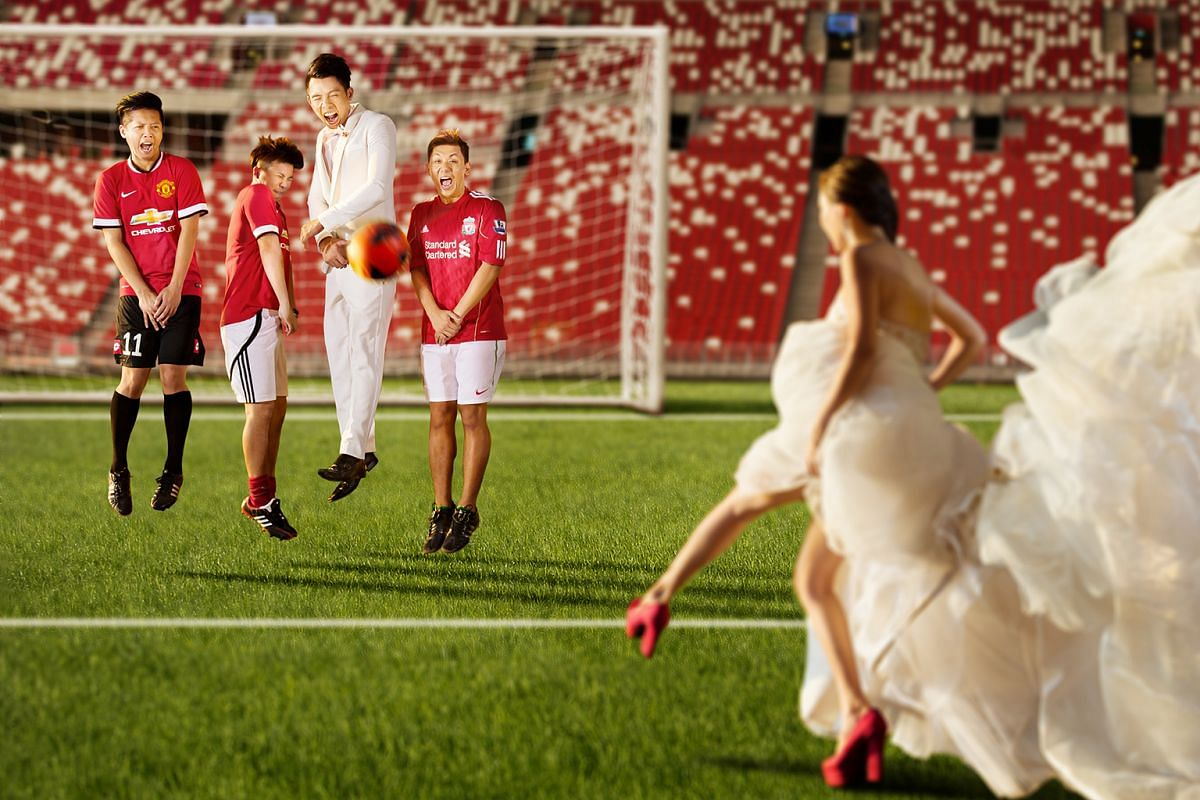 """One photo (above), taken at the National Stadium, shows Ms Ong decked out in a rented $6,000 gown and four-inch heels, kicking a ball towards a goal post """"guarded"""" by Mr Thng and his groomsmen."""