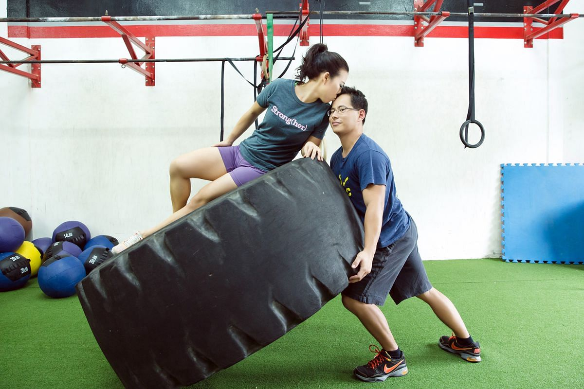 In one photo (above), Mr Tan is lifting a 250kg tyre on one side, with MsLi,who weighs 55kg, perched on top.