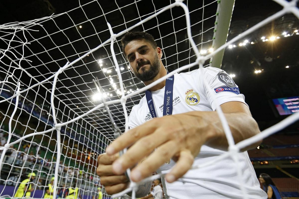 Isco cuts the net from the goalposts after winning the Uefa Champions League.