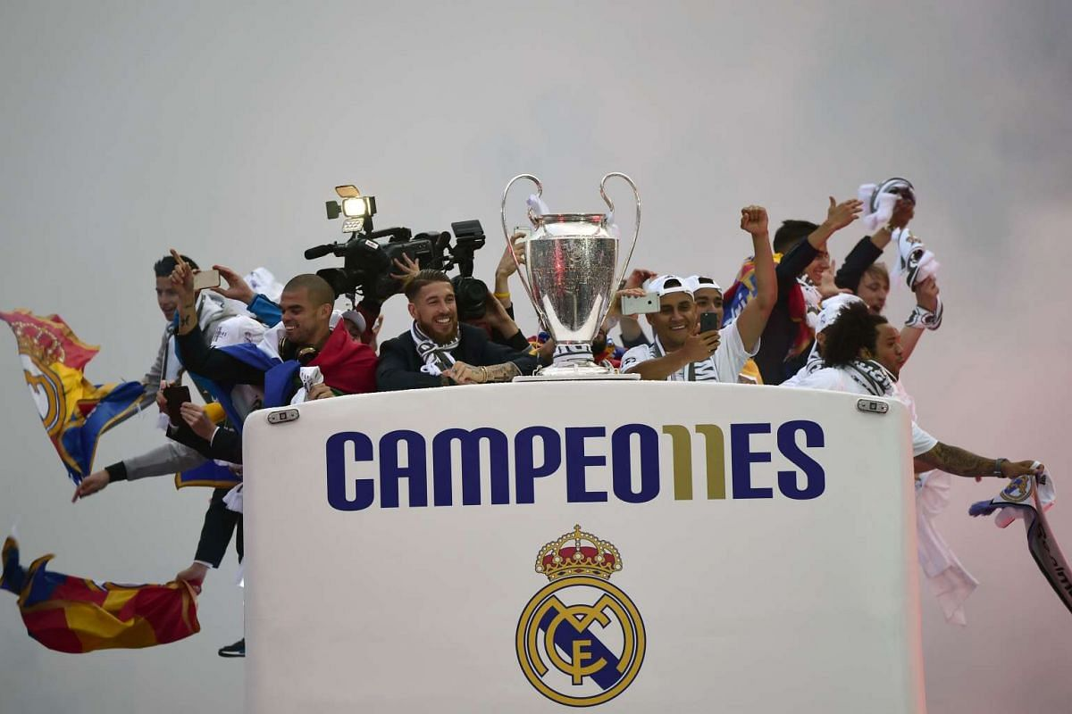 Real Madrid players hold up the trophy from the bus as they celebrate the team's win upon arriving in Plaza Cibeles in Madrid on May 29, 2016, after the UEFA Champions League final foobtall match between Real Madrid CF, Club Atletico de Madrid held i