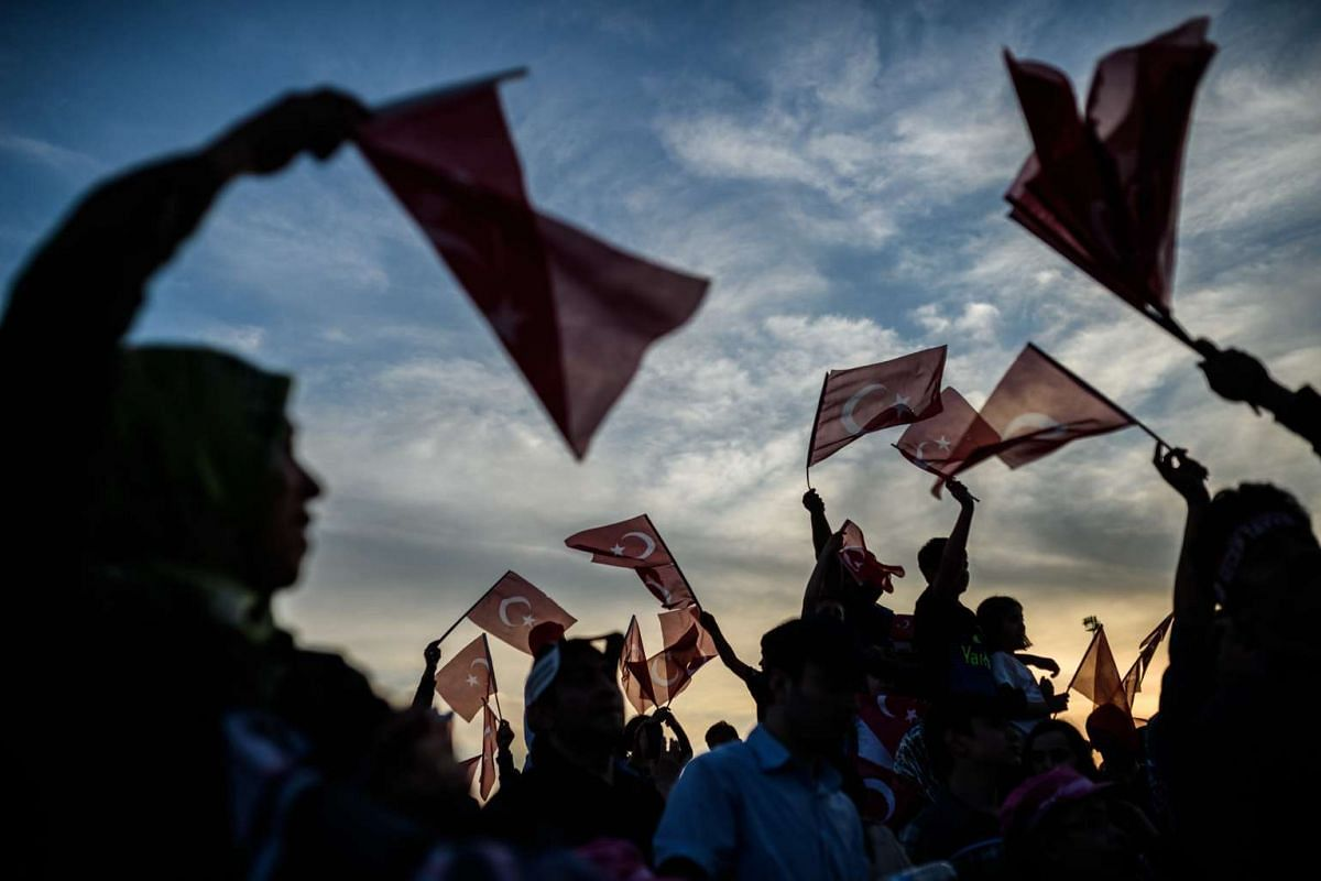 People wave Turkish national flags as Turkish President speaks during a rally to mark the 563rd anniversary of the conquest of Istanbul by Ottoman Turks on May 29, 2016 in Istanbul. PHOTO: AFP