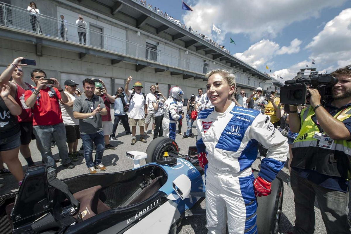 Recording artist Lady Gaga greets the public moments after taking a parade lap in a double seater Indy car driven by 1969 Indianapolis 500 champion Mario Andretti during the 100th running of the Indianapolis 500 at Indianapolis Motor Speedway on May