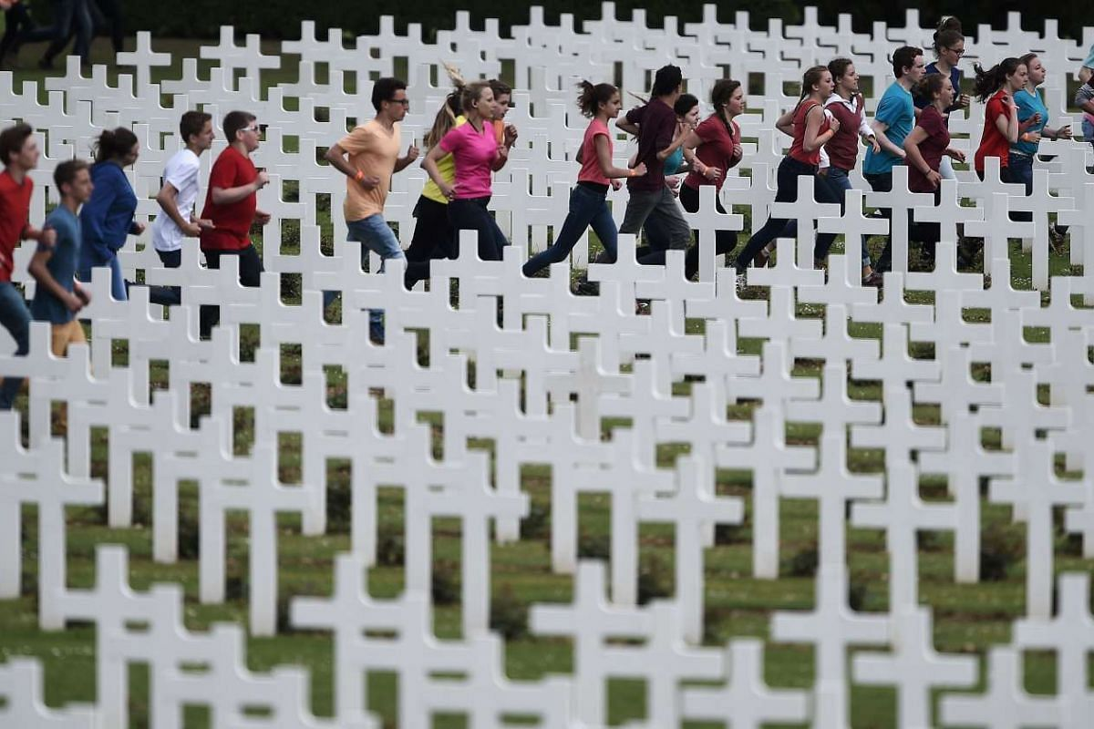 French and German youths take part in a show at the French National cemetery outside the Douaumont Ossuary (Ossuaire de Douaumont), northeastern France, on May 29, 2016, during a remembrance ceremony to mark the centenary of the battle of Verdun. PHO