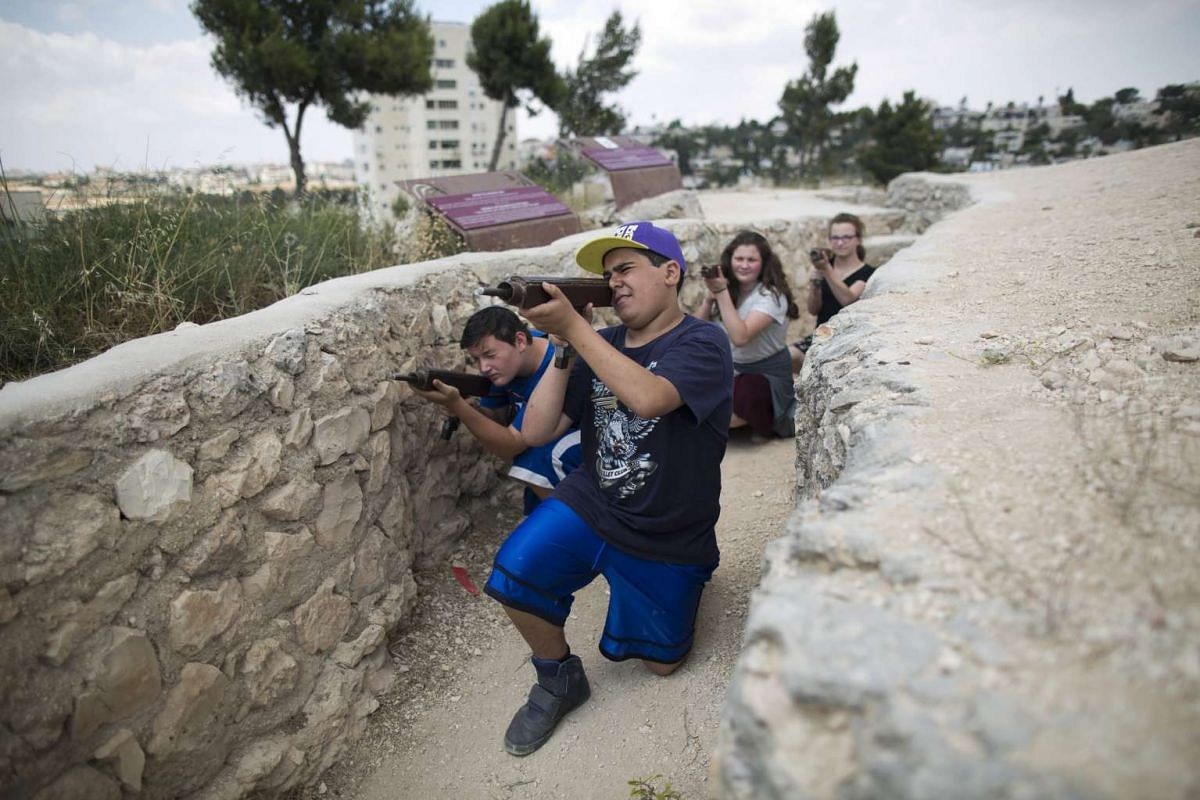 Israeli youths holding mock Israeli Uzis in an old Jordanian war trench at the 'Ammunition Hill memorial site and heritage of the battle for Jerusalem during the Six Day War (1967)' in Jerusalem, Israel, May 29, 2016. PHOTO: EPA