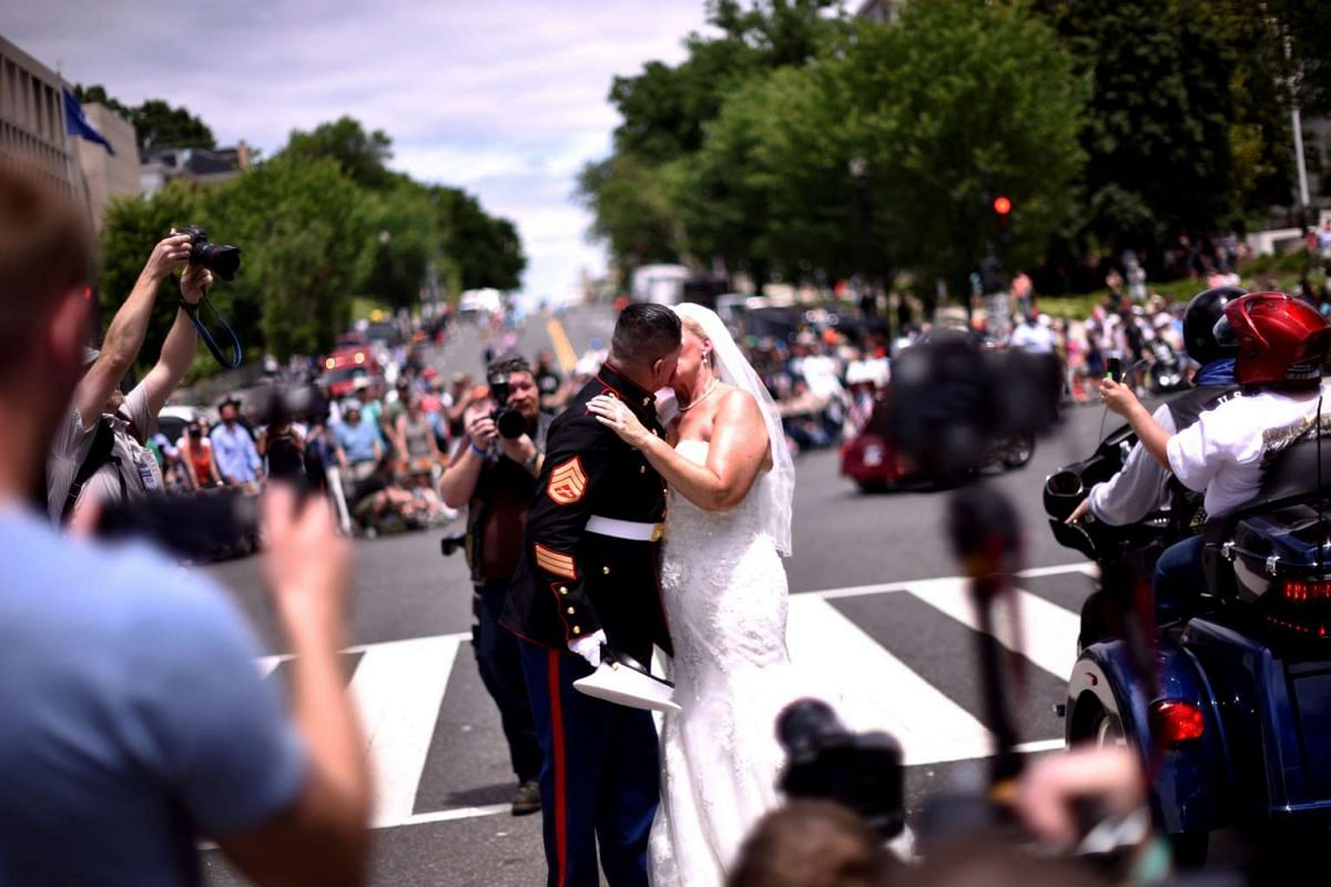 US Marine Corp Staff Sgt Tim Chambers and his bride Lorraine Heist share a kiss as they greet motorcyclists participating in Rolling Thunder, the annual ride around Washington Mall to raise awareness for prisoners of war and soldiers still missing in