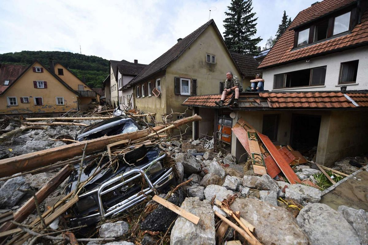 Kurt Walter, a relative of a resident sits on a garage roof and looks at debris after after heavy storms and severe weather hit parts of southern Germany casuing floods, near Braunbach, Germany, May 30, 2016. PHOTO: EPA