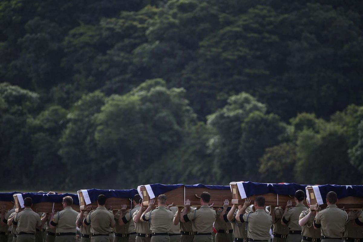 Australian military personnel carry coffins during a repatriation ceremony for Australian soldiers at the Royal Malaysian Air Force (RMAF) airbase in Subang, outside Kuala Lumpur, Malaysia, May 31, 2016. PHOTO: EPA