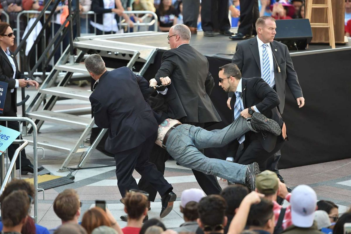Secret Service agents arrest a man for climbing over a barricade and approaching Democratic presidential candidate Bernie Sanders while he speaks at Frank Ogawa Plaza in Oakland, California on May 30, 2016. PHOTO: AFP