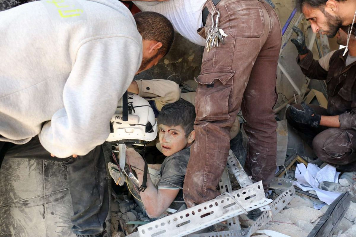 Syrian civil defence volunteers help a boy out of the rubble following a reported attack by Syrian government forces on May 30, 2016, in the Tariq al-Bab neighbourhood in the northern city of Aleppo. PHOTO: AFP