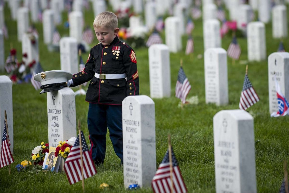 Christian Jacobs, 5, of Hertford, North Carolina, places his Marine cover on the headstone of his father, Marine Sgt. Christopher Jacobs, on Memorial Day in Section 60 at Arlington National Cemetery in Arlington, Virginia, USA, May 30, 2016. PHOTO: E