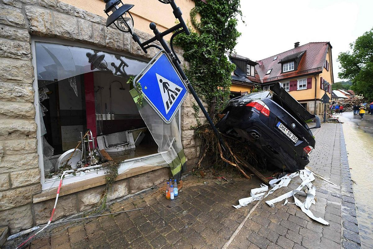 A broken window and a damaged car in Braunsbach, Germany, following a heavy storm.