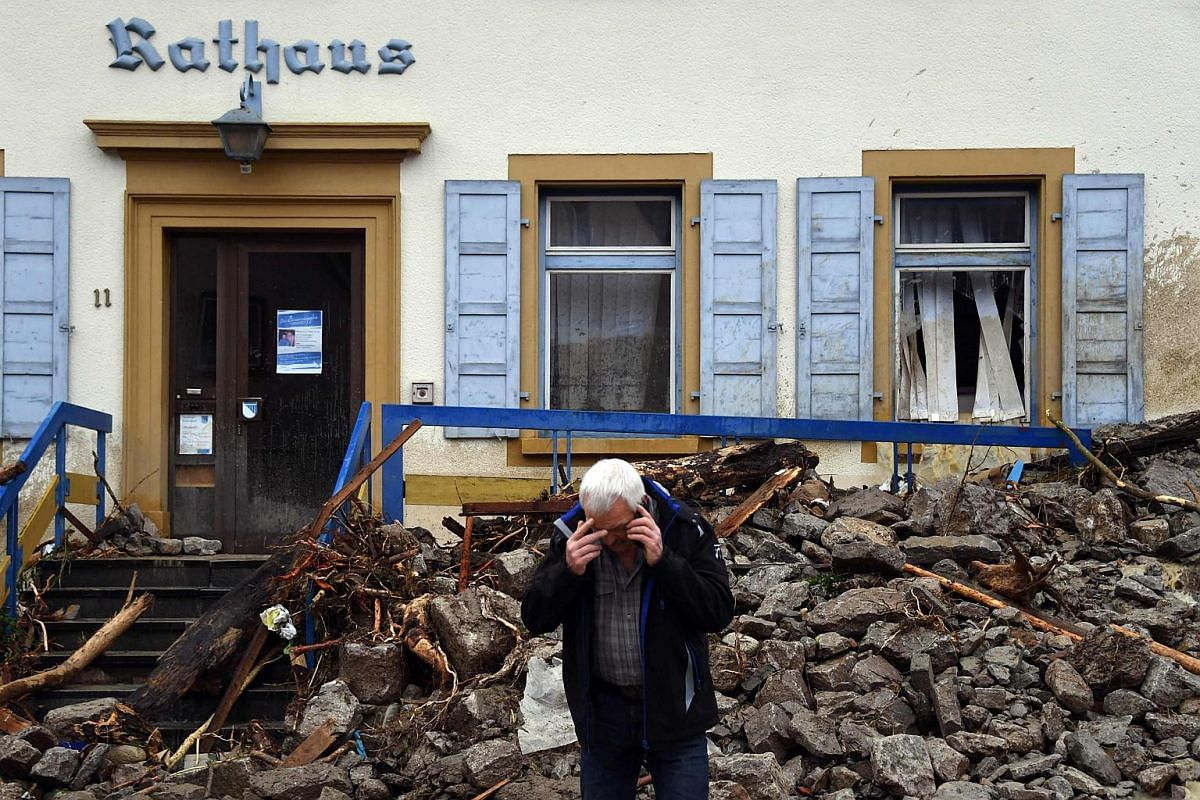 A man talks on the phone in front of the townhall in Braunsbach following a heavy storm.