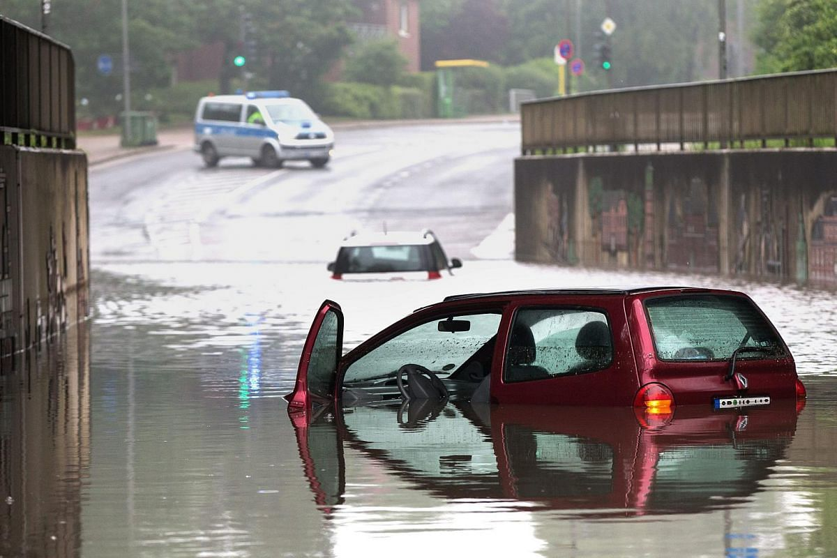 Partially submerged cars stand abandoned in a flooded underpass in Oberhausen, Germany.
