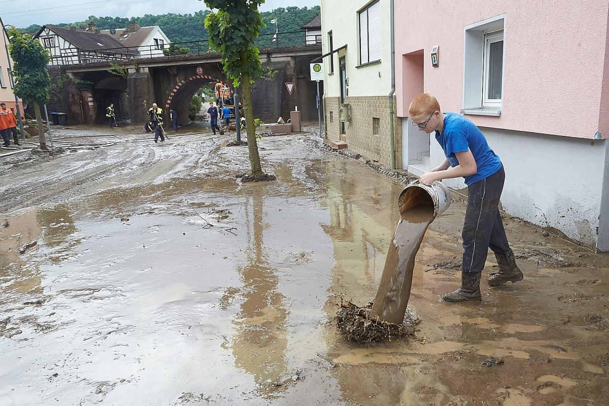 Firefighters help residents clean up a mud-covered street following a heavy storm in Wellmich, Germany, on May 30.