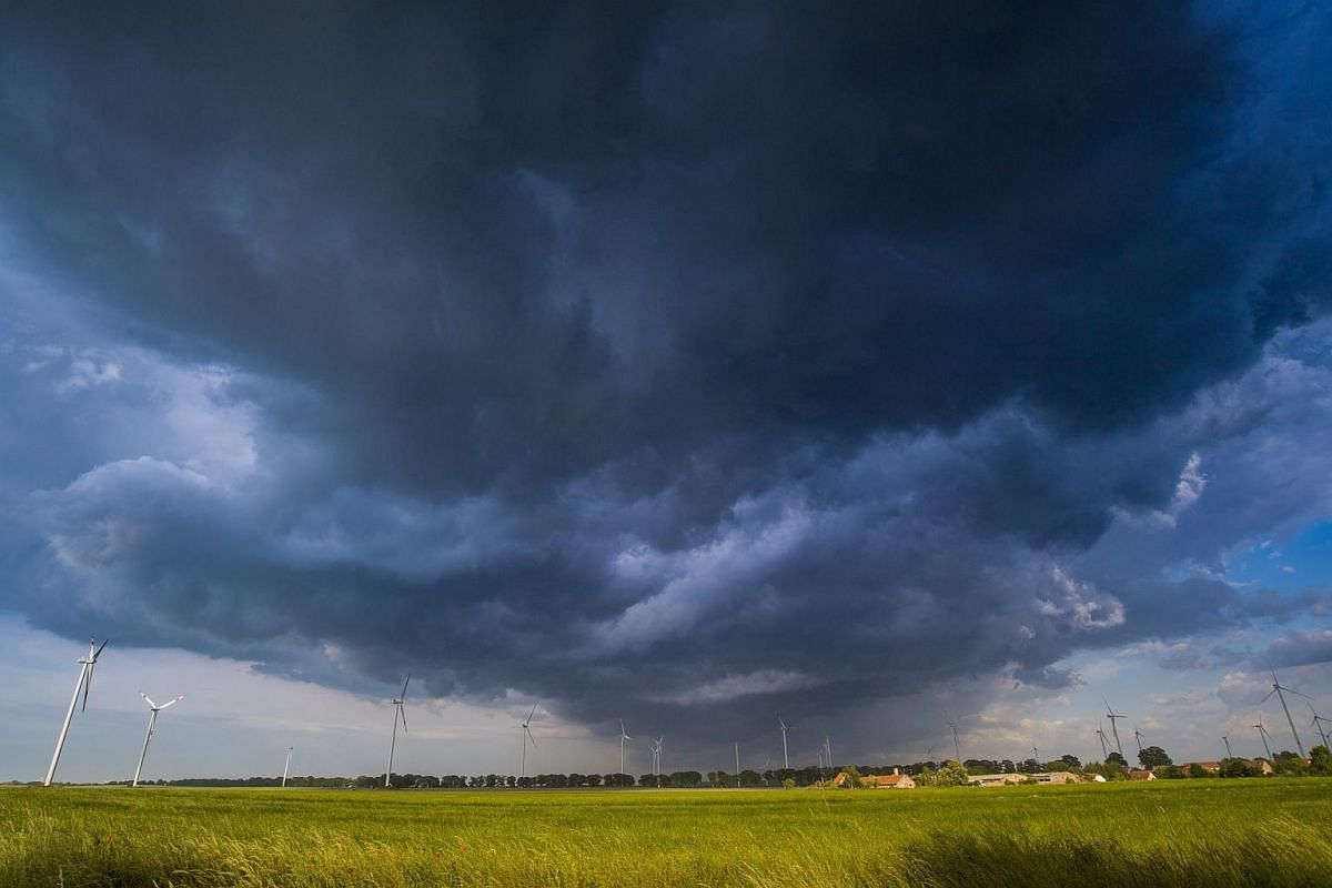 Dark, stormy clouds gather at a wheat field near Petersdorf, Germany.
