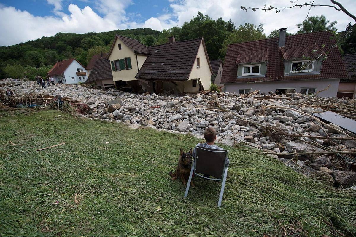 A man looks at debris in a residential street in Braunbach after heavy storms and severe weather hit parts of southern Germany causing floods.
