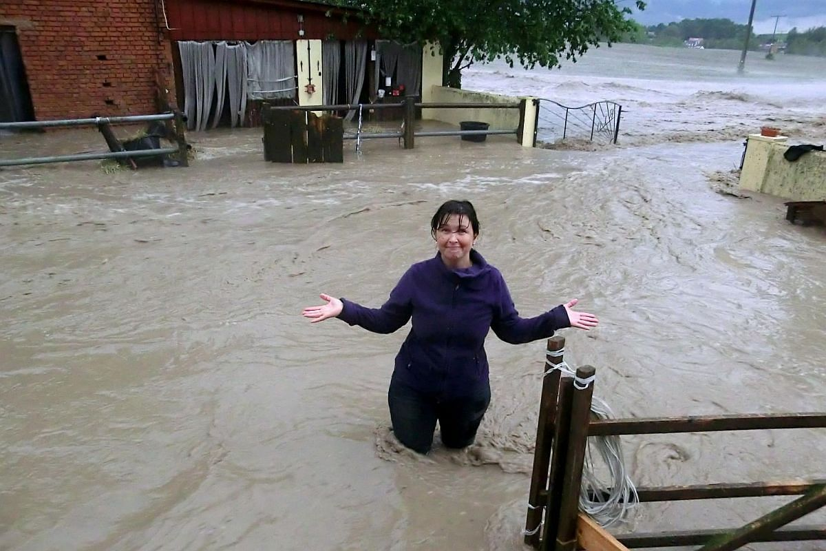 A woman stands amidst the water flooding a horse farm in Obernzenn, southern Germany, after a thunderstorm hit the region on May 29.