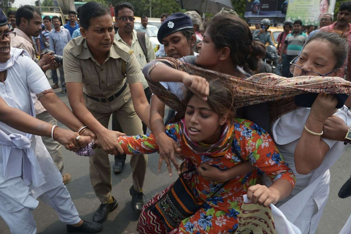 Indian police arrest activists from the Social Unity Centre of India (SUCI) organisation as they block a road during a protest against a gang rape in Kolkata, on May 31, 2016.