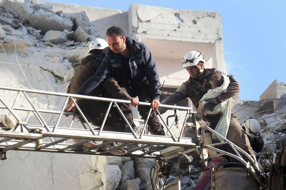 Syrian Civil Defence members evacuate a toddler from the rubble of buildings destroyed following Russian air strikes a day earlier in the city of Idlib, on May 31, 2016.