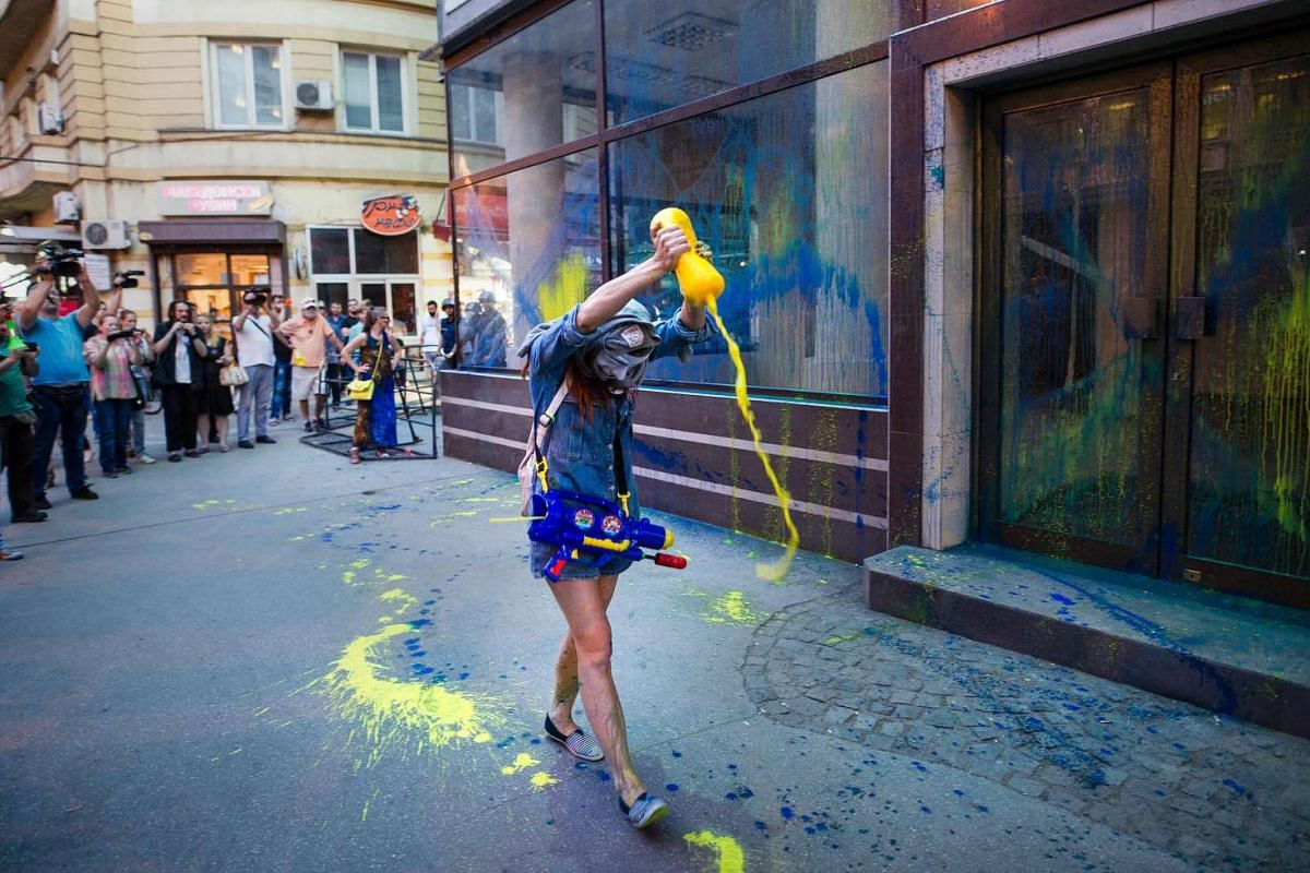 A protestor wearing a mask empties a bottle of colored paint on the public office of President Gjorge Ivanov during an anti-government protest in Skopje, on May 31, 2016.