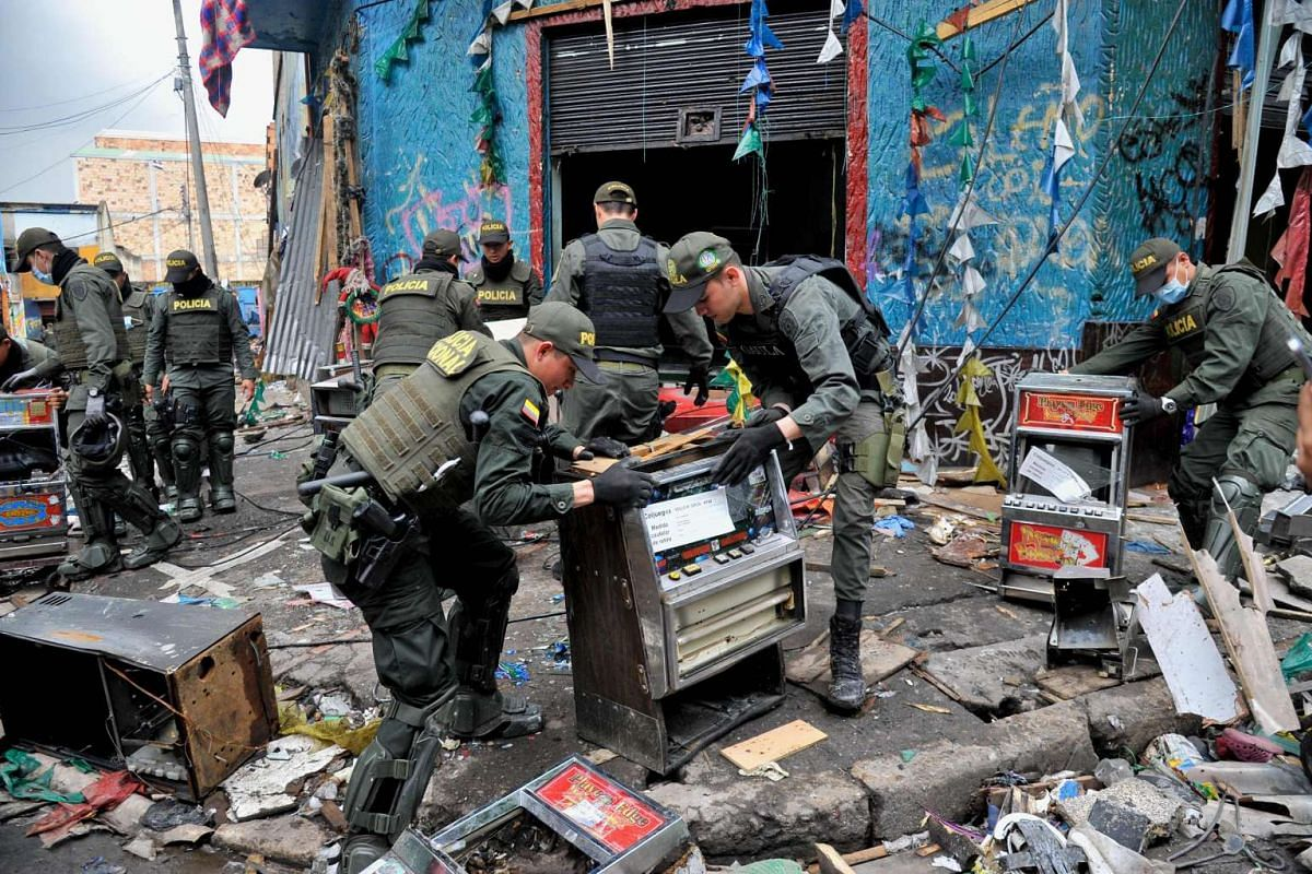 Police officers carry out an operation just days after a raid in the notorious section of Bogota known as The Bronx, plagued by rampant drug trafficking and prostitution rings, on May 31, 2016.