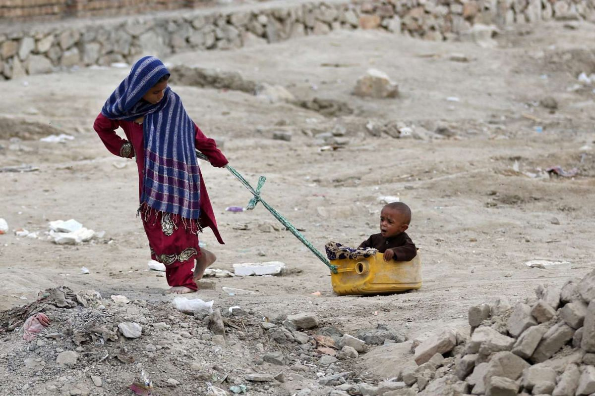 Unidentified Afghan Internally Displaced Persons (IDP) play at a temporary shelter in Kabul, Afghanistan, on May 31, 2016.