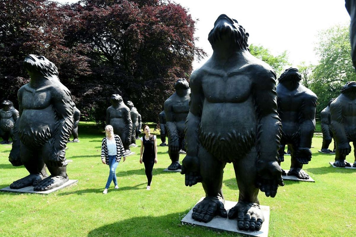 Visitors look at the sculptures, Original Sin, by Chinese artist Liu Ruowang on display as part of the NordArt 2016 international art exhibition in Buedelsdorf, Germany, on May 30, 2016.