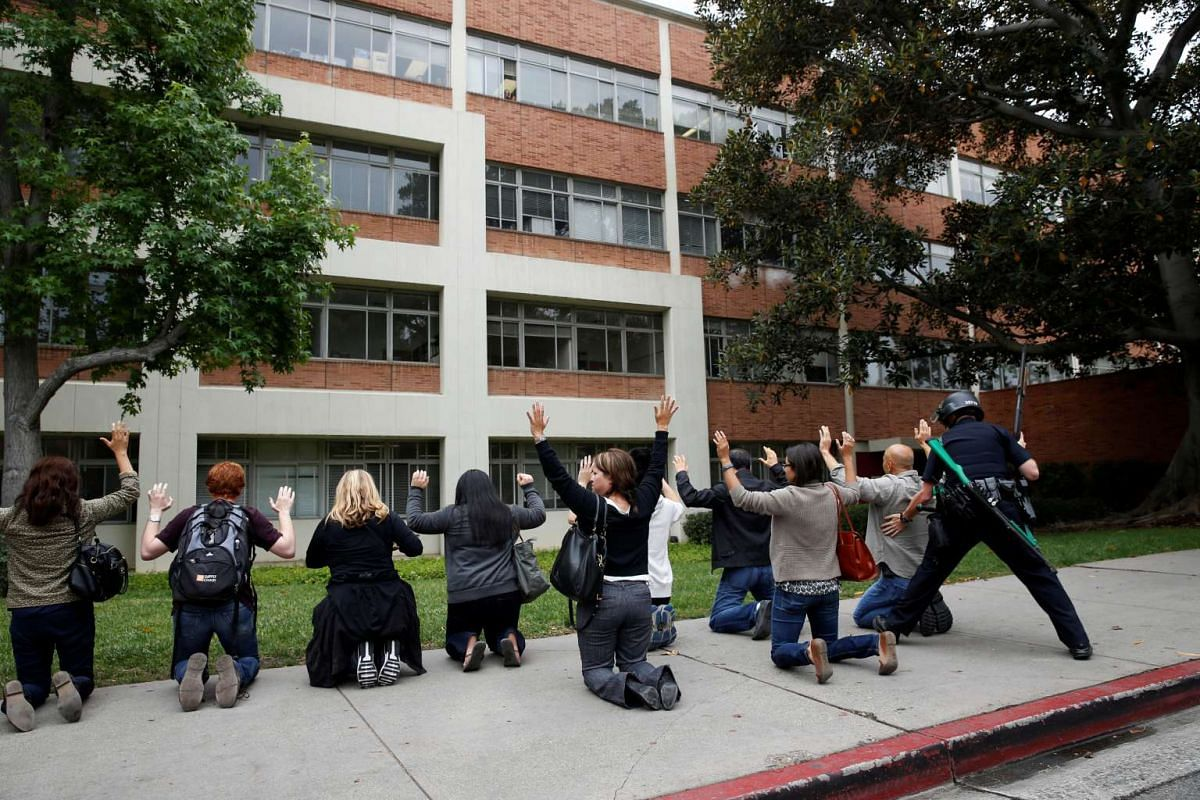 A police officer conducts a search on people at the University of California, Los Angeles (UCLA) campus after it was placed on lockdown following reports of a shooter that left 2 people dead in Los Angeles, California June 1, 2016. PHOTO: REUTERS