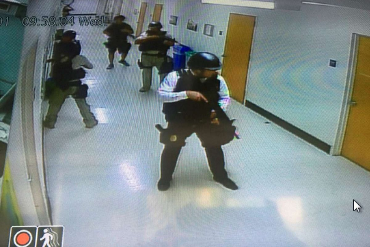Police officers search corridors and rooms after the report of an active shooter on a UCLA campus in Los Angeles, California, U.S. June 1, 2016 in a still image from a CCTV camera. PHOTO: REUTERS/HANDOUT/UCLA