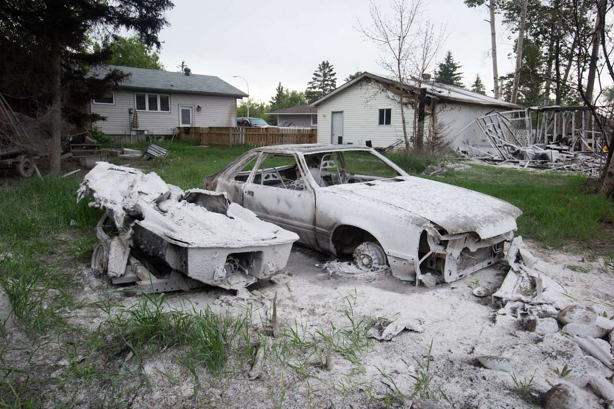 A boat and car destroyed by wildfire sit in the backyard of a house in Fort McMurray, Alberta, Canada, on Wednesday, June 1, 2016. PHOTO: BLOOMBERG