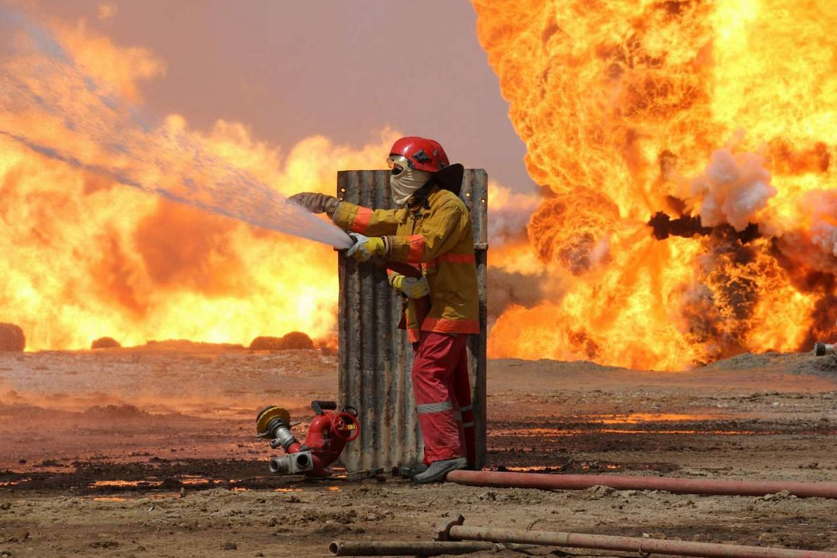 Oil workers and firemen try to extinguish flames at the Khabbaz oil field some 20 kilometres southwest of Kirkuk on June 1, 2016 following a reported improvised explosive attack by the Islamic State (IS) group. PHOTO: AFP