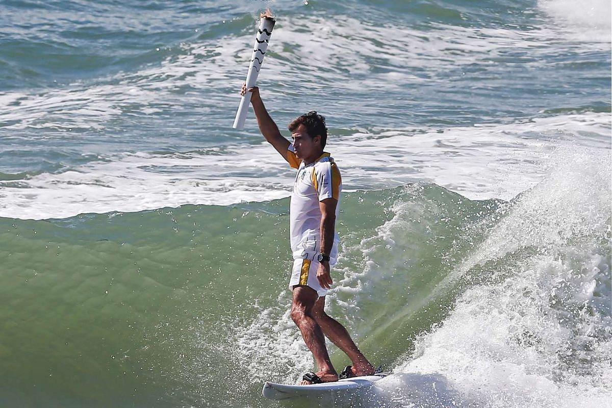 Handout picture released by RIO2016 showing Brazilian surfer Carlos Burle holding the Olympic torch as it visits Porto de Galinhas, Ipojuca, in the Brazilian norteastern state of Pernambuco on June 1, 2016. PHOTO: AFP/HANDOUT/ RIO2016