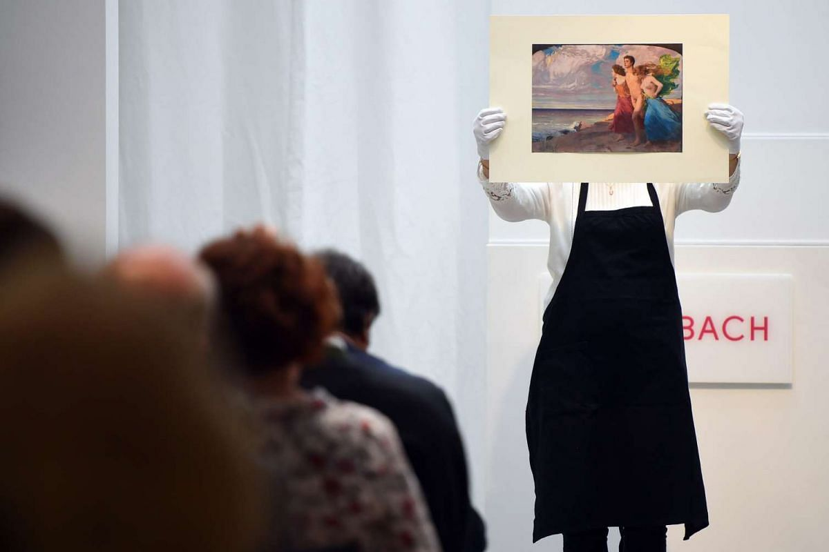 An employee of the Villa Grisebach auction house presents the painting 'Fruehlingssturm' (lit: Spring storm) by Ludwig von Hofmann at a spring sale in Berlin, Germany, June 1, 2016. PHOTO: EPA