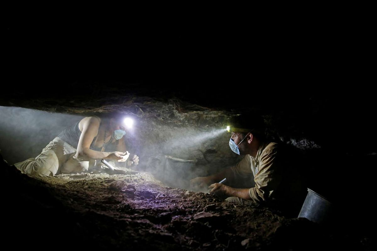 Volunteers with the Israeli Antique Authority work inside the Cave of the Skulls in the Judean Desert, in Israel, on June 1, 2016.
