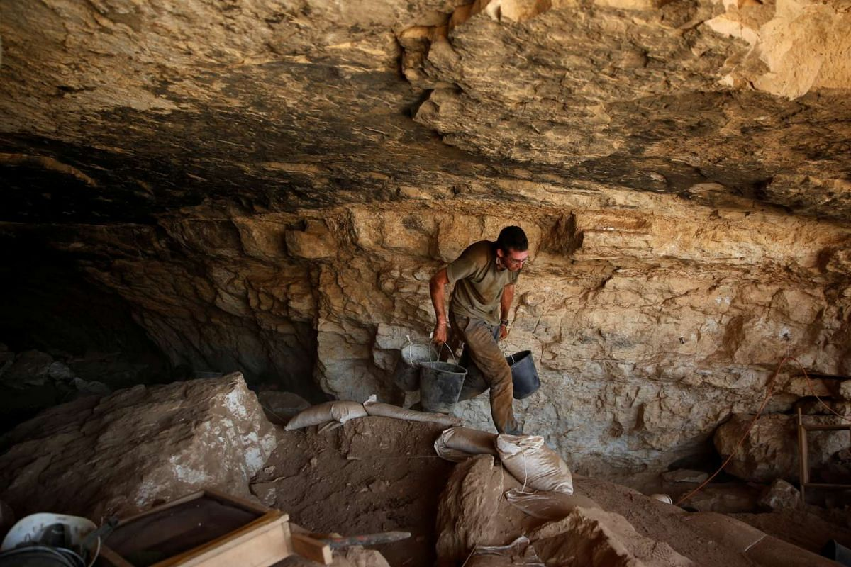 A volunteer with the Israeli Antique Authority works in the Cave of the Skulls in the Judean Desert, in Israel, on June 1,
