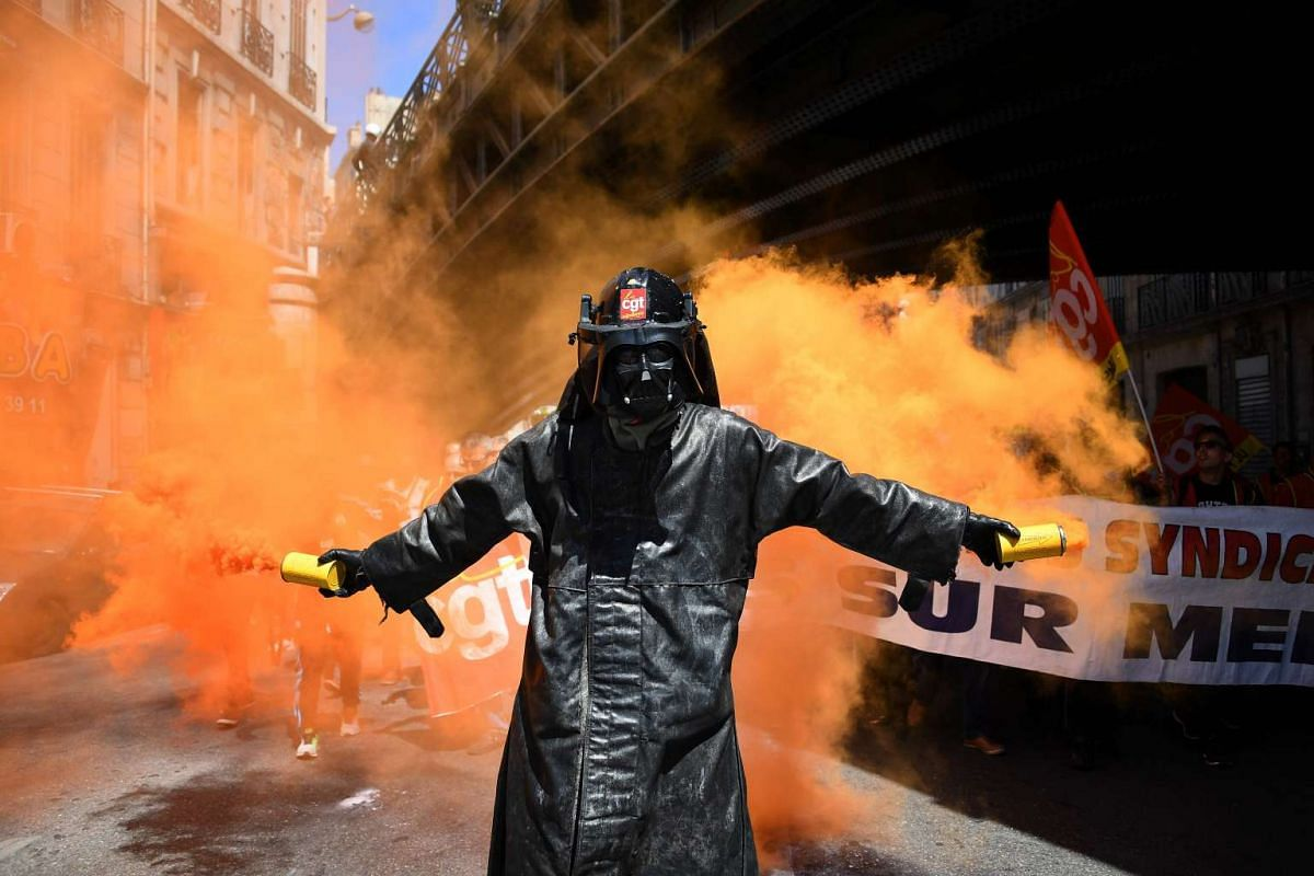 A man wearing a Darth Vader mask holds smoke flares during a demonstration against the French government's planned labour law reforms, on June 2, 2016 in Marseille, southern France. PHOTO: AFP