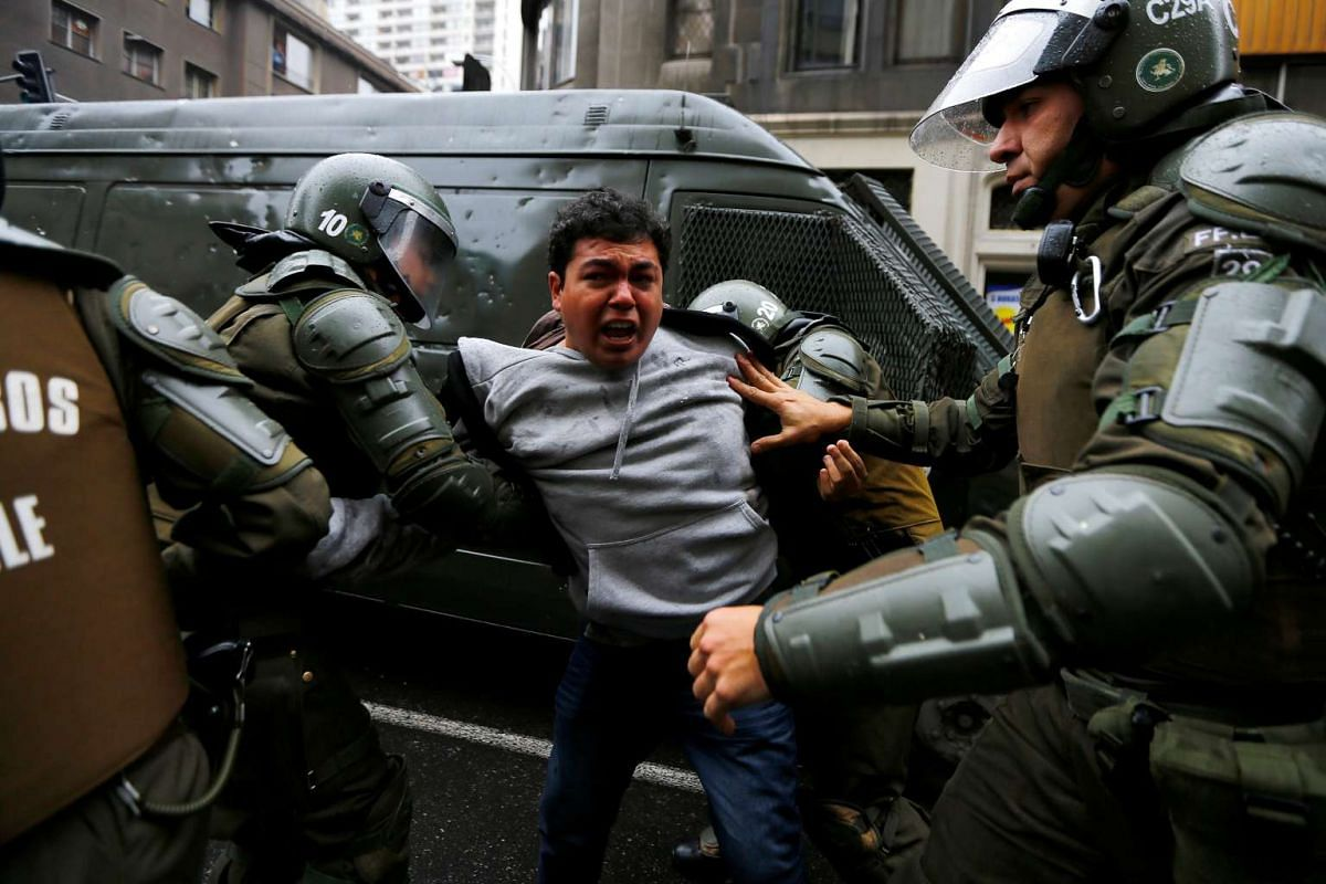 Riot policemen detain a demonstrator during an unauthorized march of a private university to protest against the government education reform in Santiago, Chile, June 2, 2016. PHOTO: REUTERS