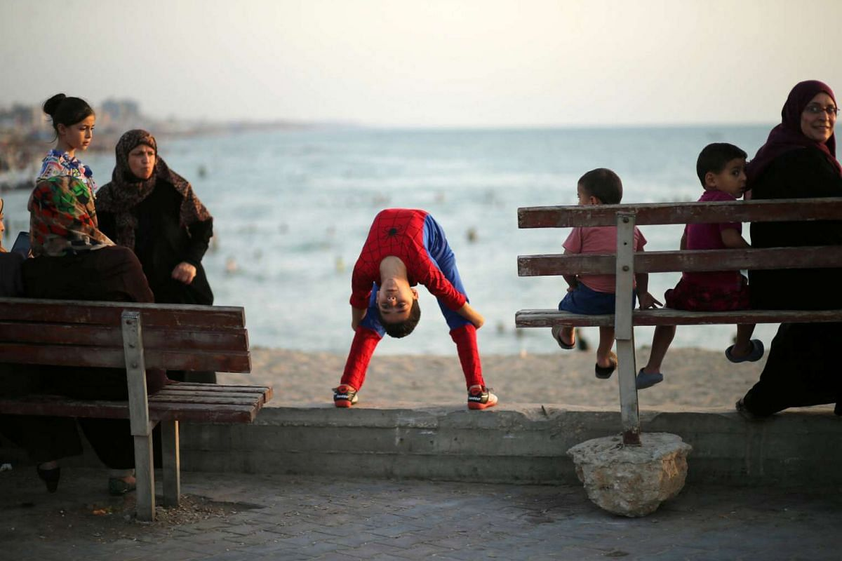 Palestinian boy Mohamad al-Sheikh, 12, who is nicknamed 'Spiderman' and hopes to break the Guinness world records with his bizarre feats of contortion, demonstrates acrobatics skills on a beach in Gaza City June 2, 2016. PHOTO: REUTERS