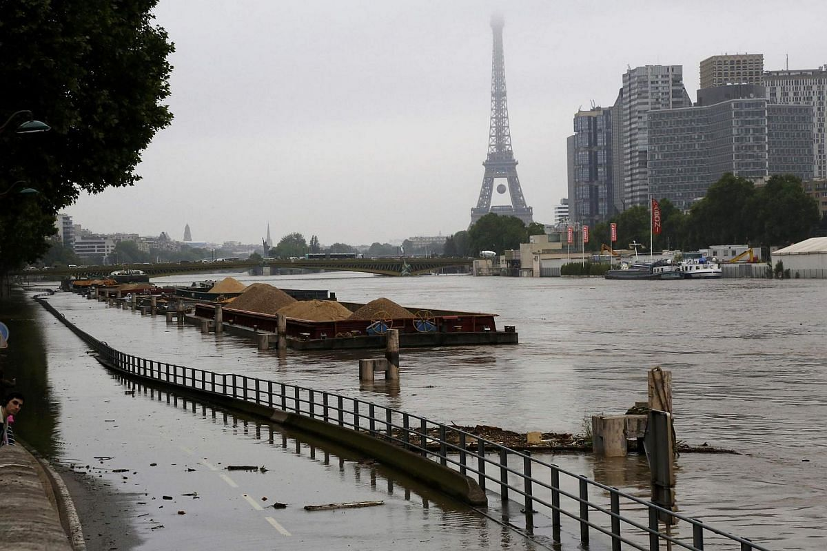 Barges are moored together near the Eiffel Tower as high waters cover the banks of the Seine River in Paris on June 2.