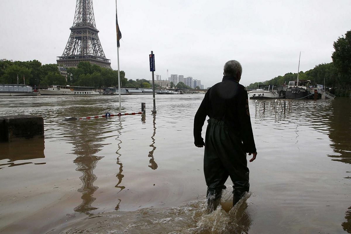 A man walks on a flooded road near his houseboat moored near the Eiffel towel during flooding on the banks of the Seine River in Paris on June 2.