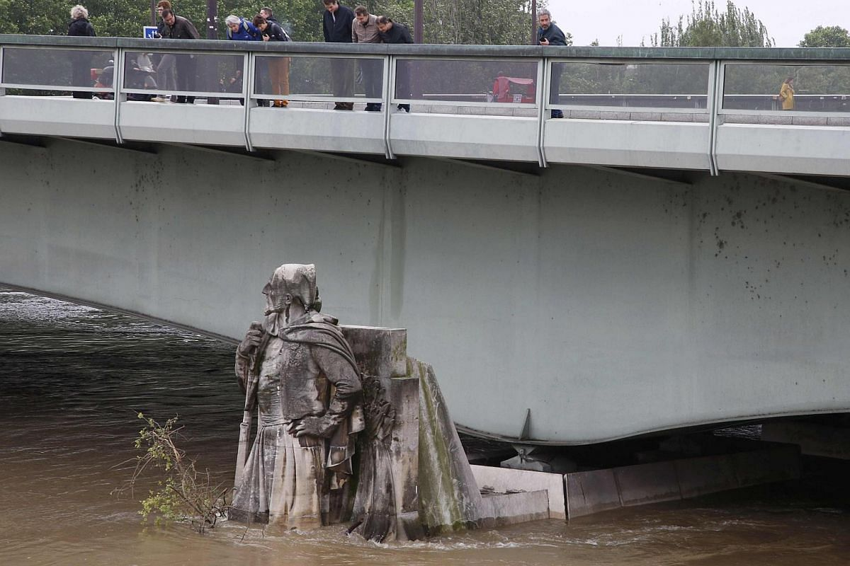People look at the Zouave statue on the Pont de l'Alma, covered by the rising waters from the Seine River in Paris on June 2.