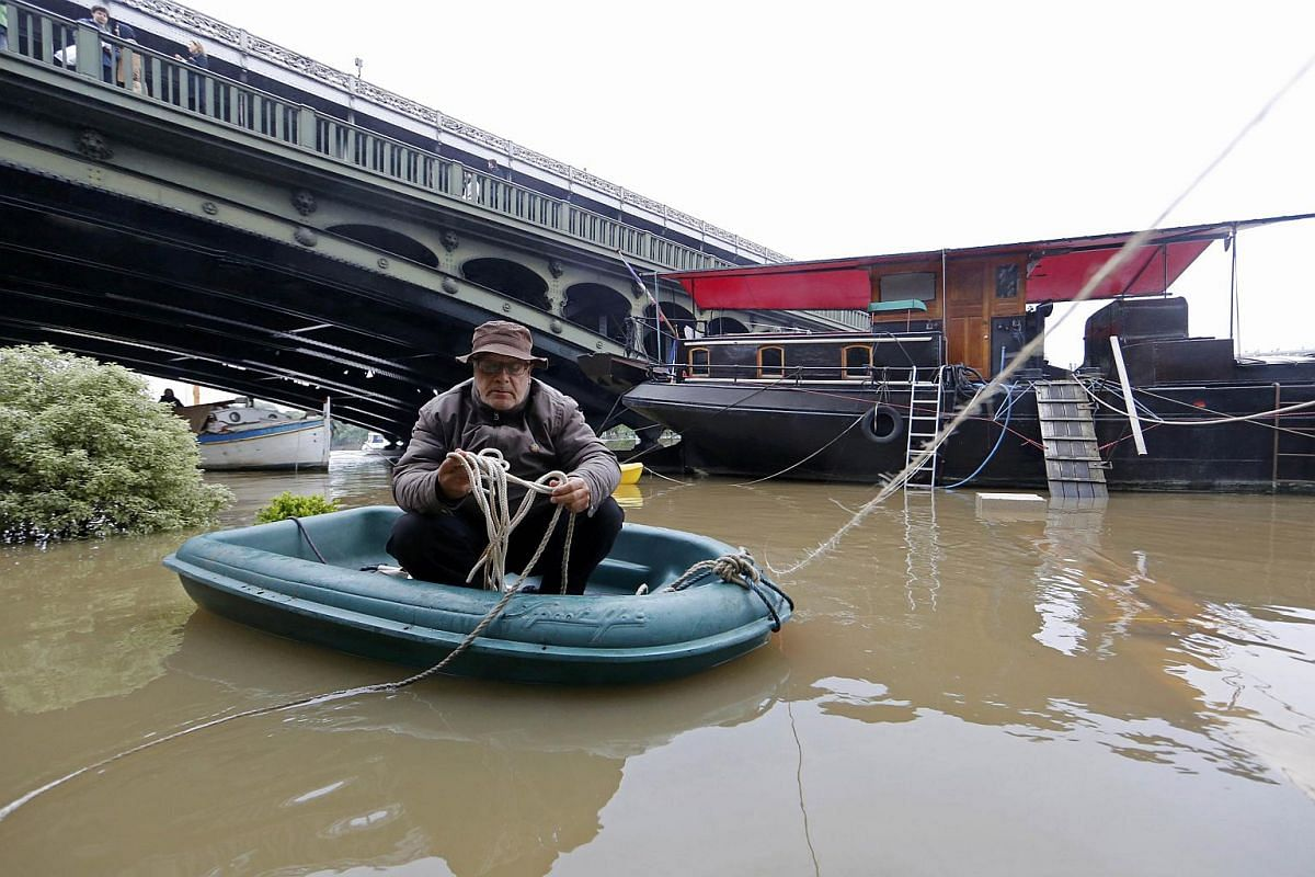 A man sits in a dinghy as he makes his way towards a houseboat along the banks of the Seine River in Paris on June 2.