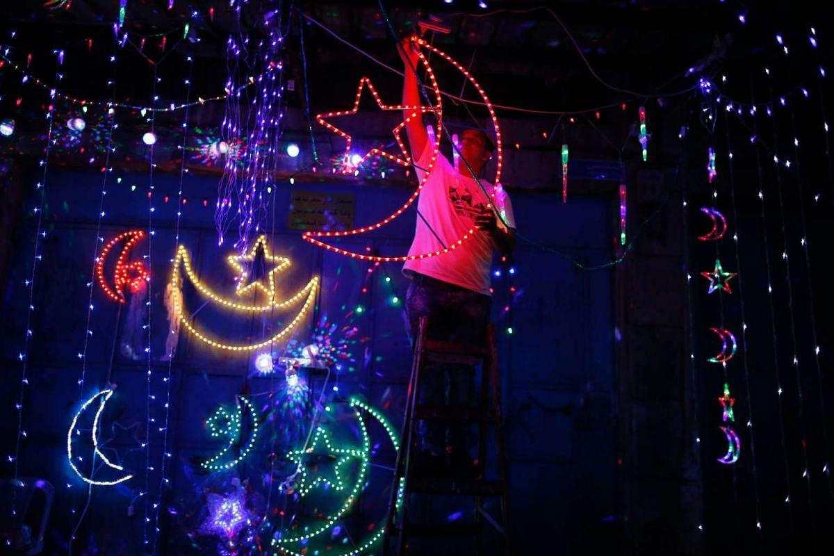 A Palestinian man decorates his shop with fairy lights in the old city of Jerusalem on June 3, 2016, as Muslims around the world prepare for the announcement of the fasting month of Ramadan.