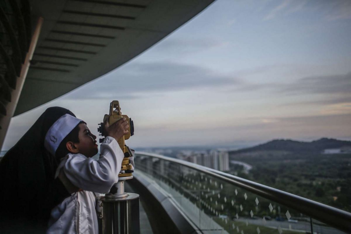A mother holds her son to look at a theodolite to determine the sighting of the new moon to mark the start of the fasting month of Ramadan in Putrajaya, outside Kuala Lumpur, Malaysia, on June 5, 2016.