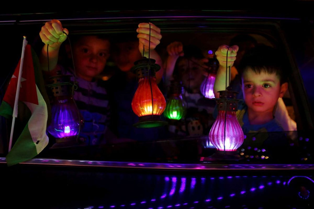 "Jordanian children hold traditional lanterns known in Arabic as ""Fanous"" in the capital Amman on June 5, 2016, as the fasting month begins."