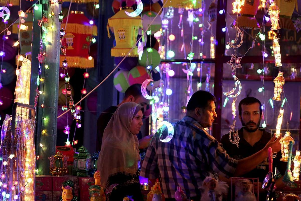 Palestinians buy traditional Ramadan lanterns in celebration the first day of the Muslim holy month of Ramadan at a shop in Gaza City, Gaza Strip on June 6, 2016.