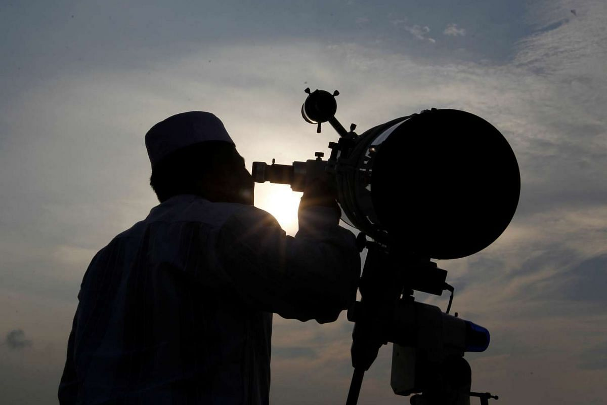 A man uses a telescope to observe the new moon before the Muslim holy month of Ramadan at Al-Musyari'in mosque in Jakarta, Indonesia, on June 5, 2016.