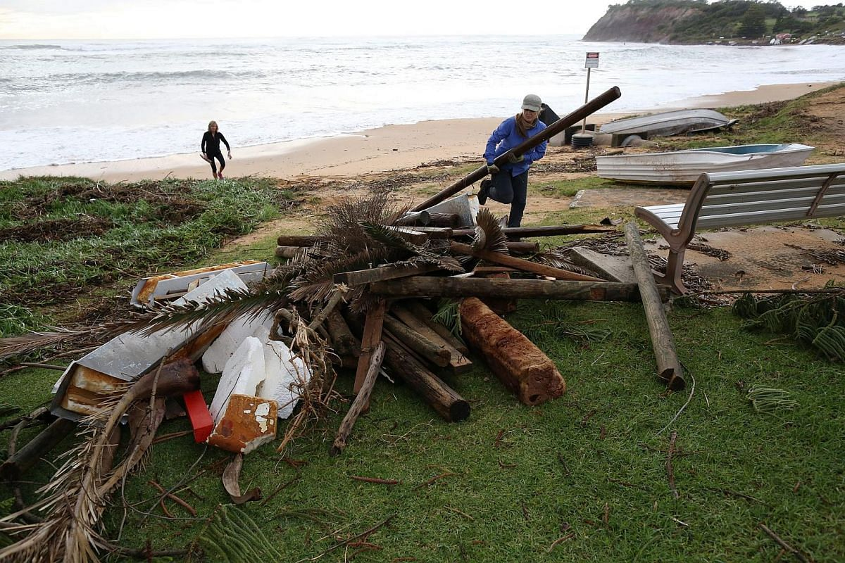 Women collect debris washed ashore after heavy rain and storms at Collaroy in Sydney's Northern Beaches, NSW, Australia, on June 5.
