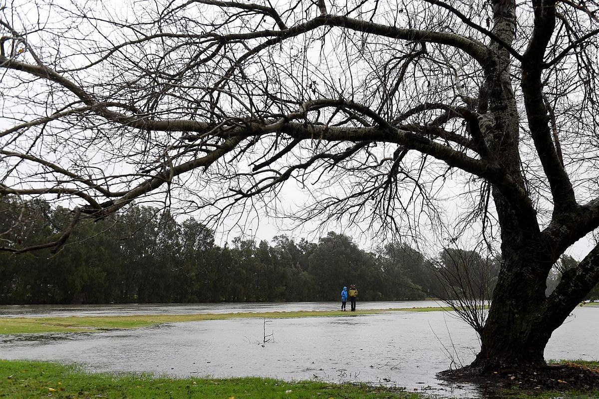 Residents walk along the banks of the Cooks River and a partially flooded golf course in Sydney, NSW, Australia, on June 5.