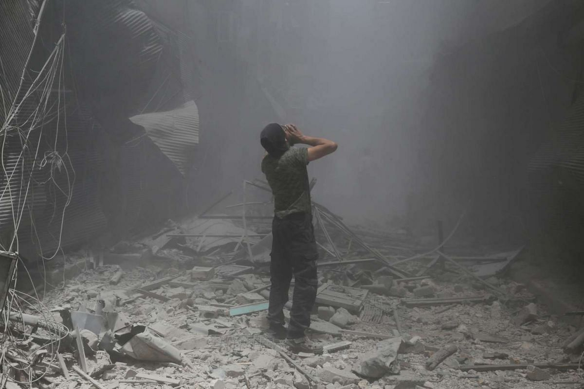 A Syrian man reacts after a reported air strike by Syrian government forces in the rebel-held neighbourhood of Bustan al-Qasr, on June 5, 2016.